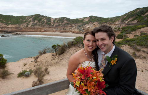 Wedding Photography showing a Melbourne bridal couple on a lookout above an ocean beach.