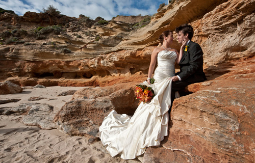 Wedding Photographers Melbourne captured this image of a newly wed couple against a background of sculpted sandstone on the ocean beach.