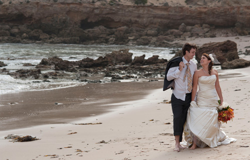 A Wedding Photo by Melbourne Photographer Pete Lorocco showing a bridal couple walking along the shore
