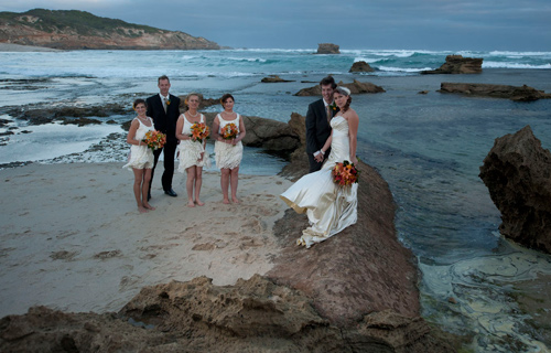 Wedding Photographers Melbourne captured this image of a newly wed couple and their bridal party, amongst tidal rock pools on the ocean beach.