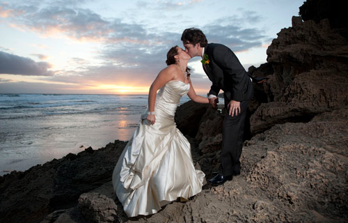 Welbourne Wedding Photography of a bride and groom kissing at sunset on the beach.