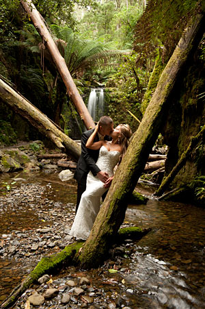 A wedding couple feature in this photo of a magnificent waterfall setting.