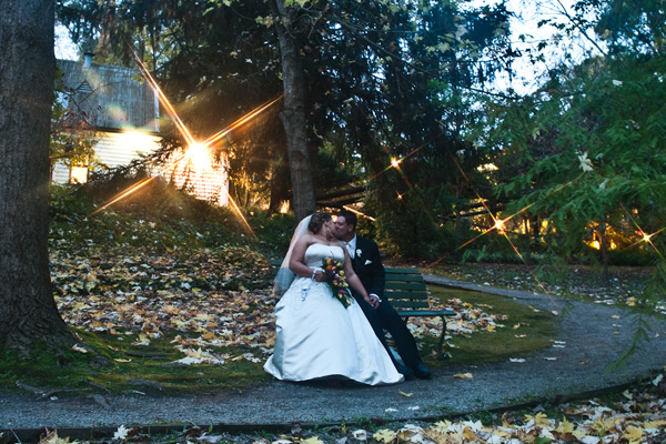 Wedding Photography at Melbourne venue Chateau Wyuna, with a bride and groom together on  garden bench seat
