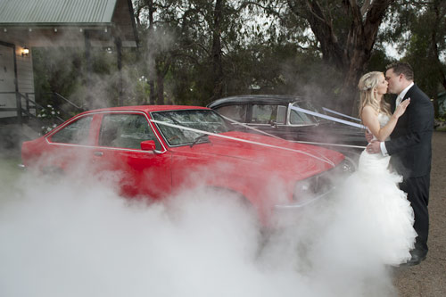 Artistic Wedding Photography- showing a bridal car doing a burnout with newlyweds kissing.