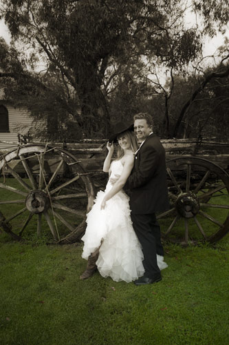 A rainy day wedding photo of a bridal couple next to an old wagon at Whitechapel receptions, Melbourne