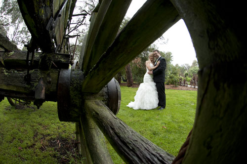 Old wheel spokes from a rustic wagon frame a bridal couple in this artistic photography composition