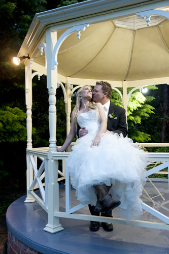 This wedding photography night shot, shows a bridal couple kissing on the gazebo at Whitechapel.