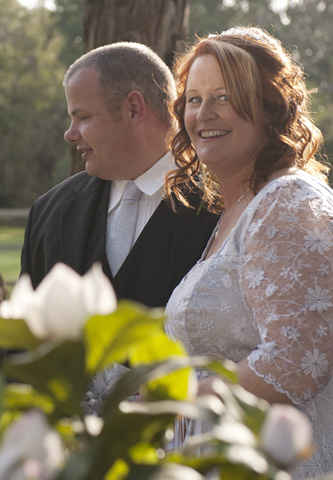 A natural candid wedding photo showing the bride laughing and the groom in the background