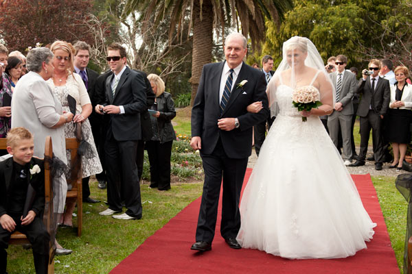 Wedding portrait photography of a bride walking down the aisle at her Warrook Cattle Farm wedding.