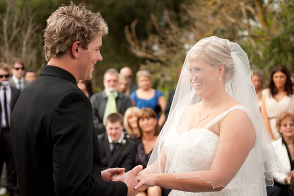 The bride smiles at her groom, during their warrook farm wedding.