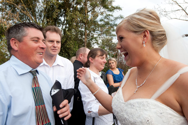 A bride laughs with guests after her wedding ceremony at Warrook farm