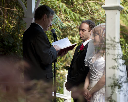 The minister reads to a bride and groom at their Lyrebird Falls wedding.