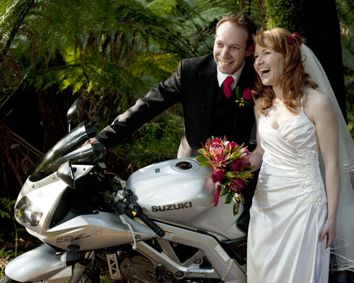 The newlyweds pose with a motorbike after their wedding at Lyrebird Falls.