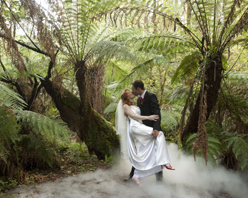 The groom kisses the bride, as mist rests on the forest floor.