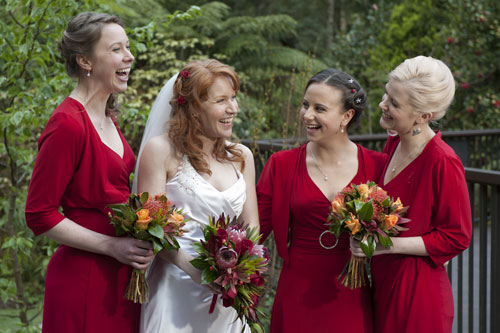A bride shares a candid moment with her bridesmaids at Lyrebird Falls, Melbourne.