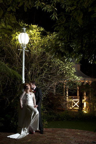 A bride and groom share a passionate kiss beneath a single lamp