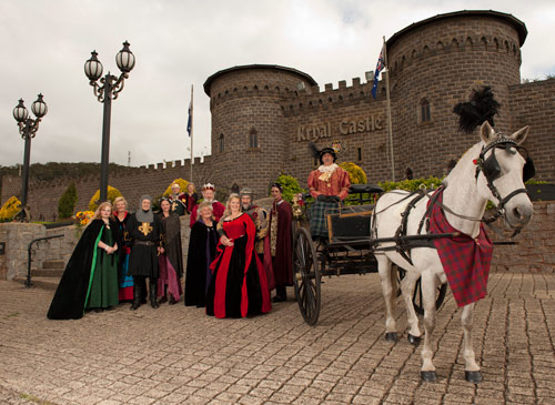 A bride and groom and their bridal party pose with a horse drawn open carriage at Kryal Castle Ballarat.