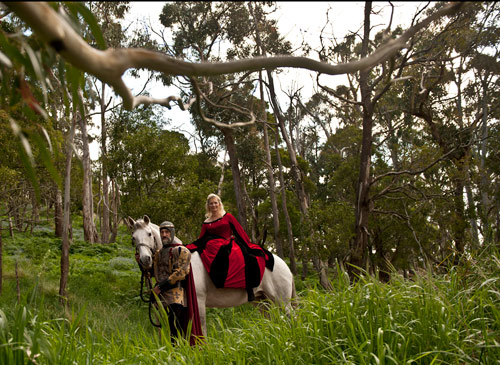 A bride on horseback is lead down a forest track by her groom at Kryal Castle Ballarat.