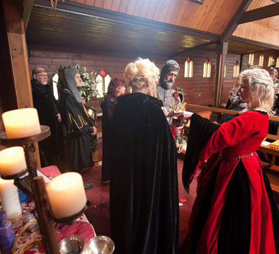 A bride and Groom exchange vows during their medieval wedding ceremony