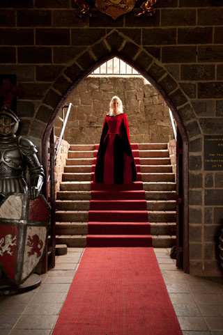The entrance arch at Kryal Castle frames this beautiful portrait of a bride in a red and black wedding dress.