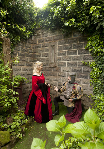 The groom kneels before the bride in this medieval wedding photo taken at Kryal Castle Ballarat.
