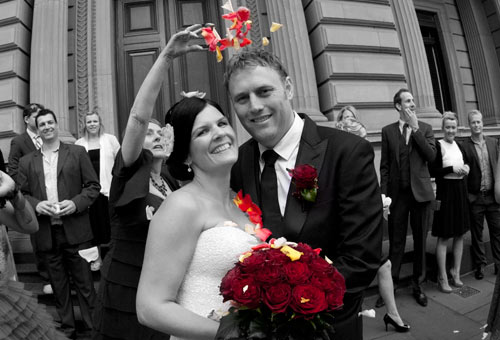 A bride and groom with rose petals on them after their Melbourne Registry Office wedding.