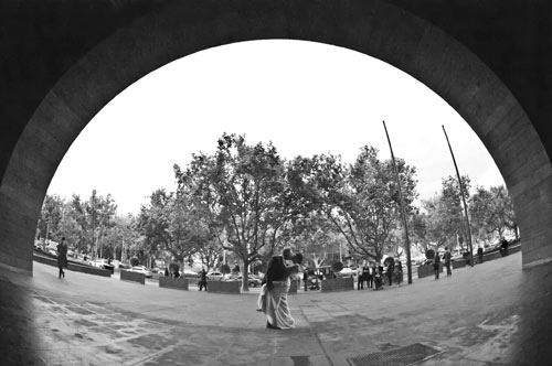 A bride and groom kissing, framed by the arch outside the National Gallery of Victoria.