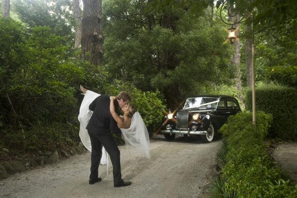 A wedding photo taken at Poets Lane, which shows the groom holding his bride in his arms with the wedding car in the background.