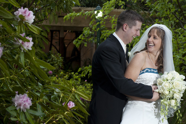 A bridal couple share a happy moment in the garden after their wedding at Poets Lane.