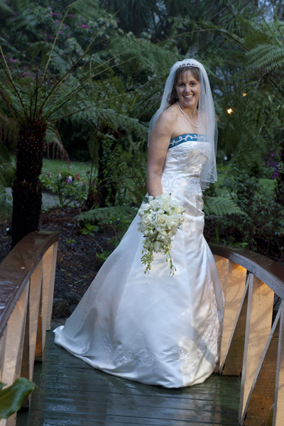 A wedding photo showing a bride on the bridge, taken in pouring rain at poets lane receptions.