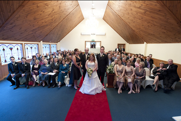 A group photo taken of everyone present, in the chapel after a poets lane wedding.