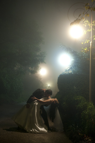 The groom holds the bride in his arms, in this beautiful misty nightshot taken during light rain.