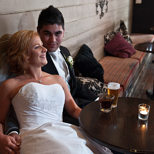 Newlyweds enjoying a dring in a tavern-like bar setting.