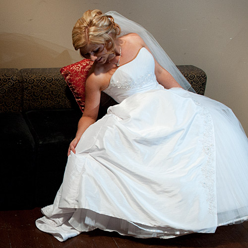 A bride looking at her gown, in an olde worlde setting