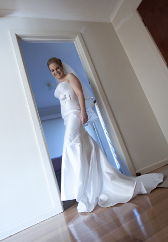 A bride poses in the doorway before her wedding at Potters Reception