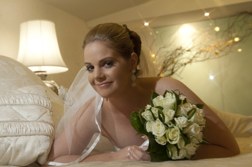 A bride relaxes on the bed at Potters Reception