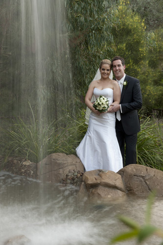 A wedding photo outside Potters Reception, showing the water feature in the front of the venue.