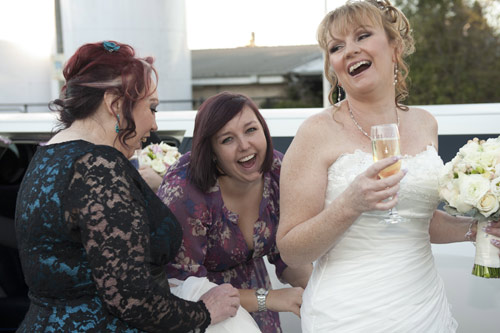 Bride laughs after alighting from limousine at her wedding