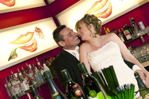 newlyweds share a kiss behind the bar at All Smiles, Warranwood.