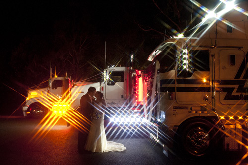 night shot of couple kissing by truck