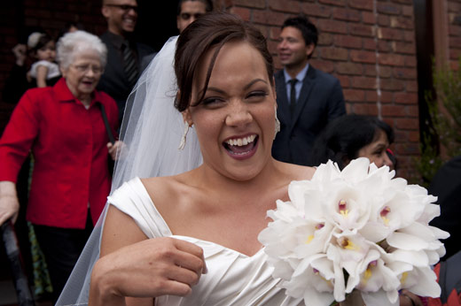 bride laughs outside church after wedding